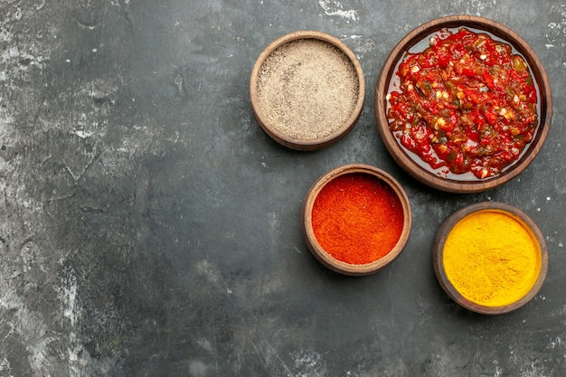 Vista de cima, deliciosa pimenta adjika em tigelas sobre fundo cinza