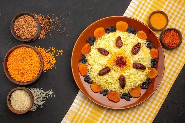 Vista de cima deliciosa plov com passas diferentes no chão escuro cozinhando comida oriental jantar de arroz