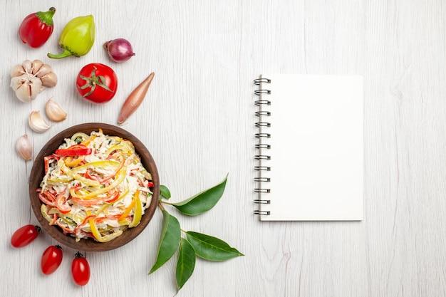 Vista de cima deliciosa salada de frango com mayyonaise e vegetais na mesa branca salgadinhos de carne madura salada de refeição fresca
