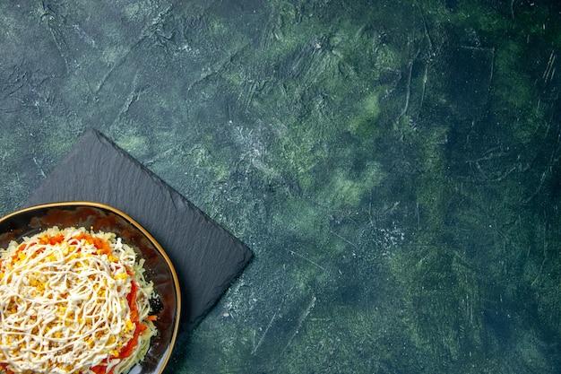Vista de cima deliciosa salada de mimosa dentro do prato em fundo azul escuro