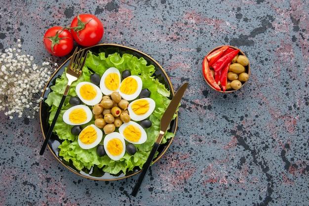 Vista de cima deliciosa salada de ovo com tomate e azeitonas em fundo claro