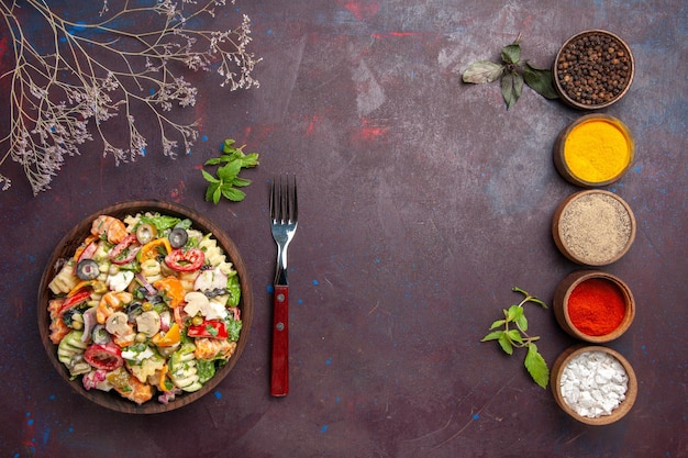 Vista de cima deliciosa salada de vegetais com diferentes temperos em piso escuro, dieta saudável, salada de vegetais, almoço