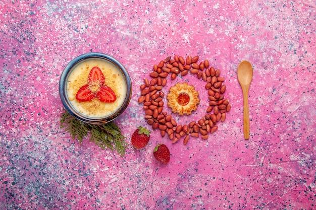 Vista de cima deliciosa sobremesa cremosa com fatias vermelhas de morangos e amendoim no fundo rosa claro sobremesa sorvete cor doce fruta baga