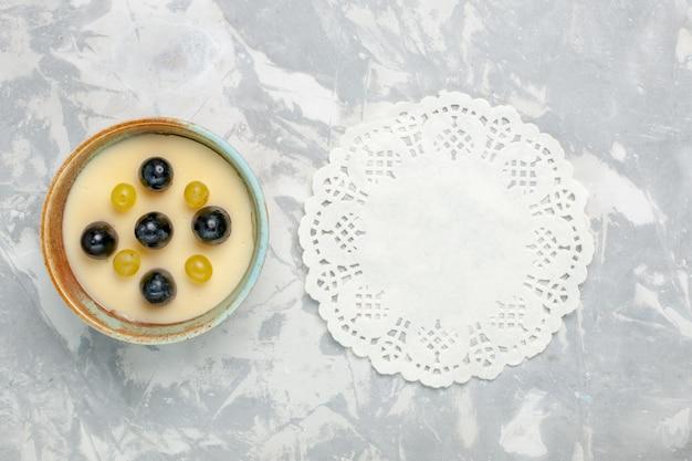 Vista de cima deliciosa sobremesa cremosa com frutas por cima dentro de uma pequena panela na superfície branca clara creme de frutas sobremesa sorvete doce de gelo