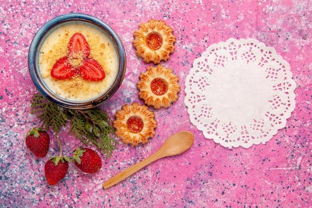 Vista de cima deliciosa sobremesa cremosa com morangos fatiados em fatias vermelhas e bolinhos no fundo rosa.
