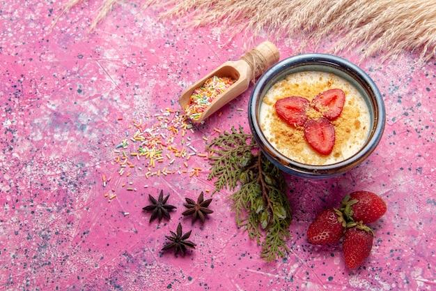 Vista de cima deliciosa sobremesa cremosa com morangos fatiados vermelhos em fundo rosa claro sobremesa sorvete de frutas vermelhas