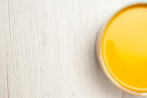 Vista de cima deliciosa sopa de creme sopa de cor amarela na mesa branca molho de sopa refeição prato de creme jantar