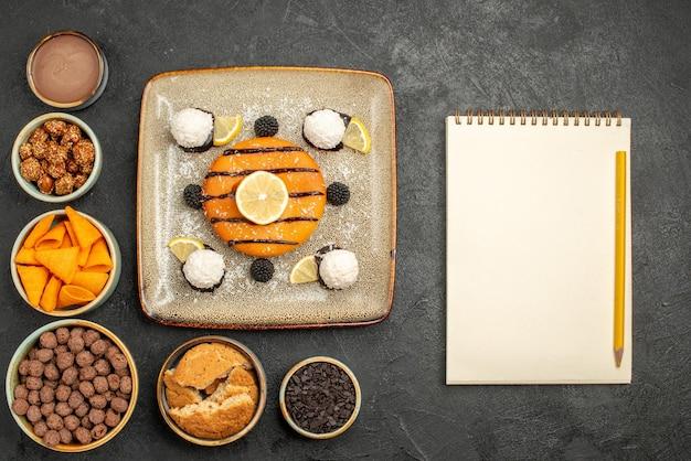 Vista de cima deliciosa torta com balas de coco em fundo cinza escuro.