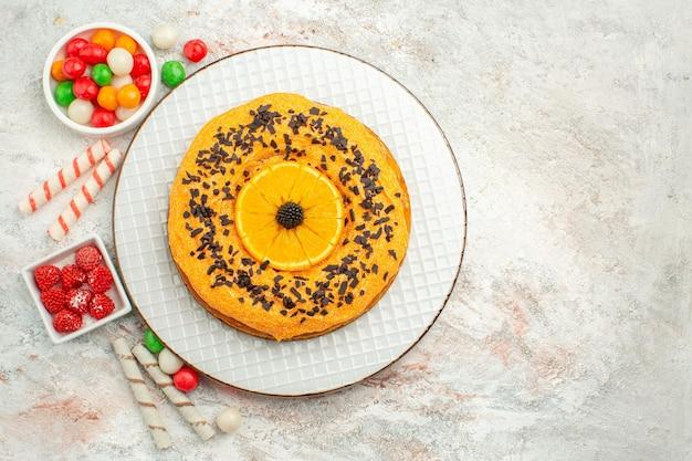 Vista de cima deliciosa torta com doces coloridos na superfície branca torta biscoito doce bolo sobremesa arco-íris