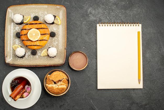 Vista de cima deliciosa torta com doces de coco e uma xícara de chá no fundo escuro.