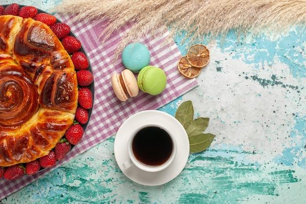 Vista de cima deliciosa torta com macarons de morangos e uma xícara de chá na superfície azul