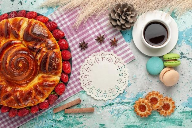 Vista de cima deliciosa torta com macarons de morangos vermelhos frescos e uma xícara de chá na mesa azul