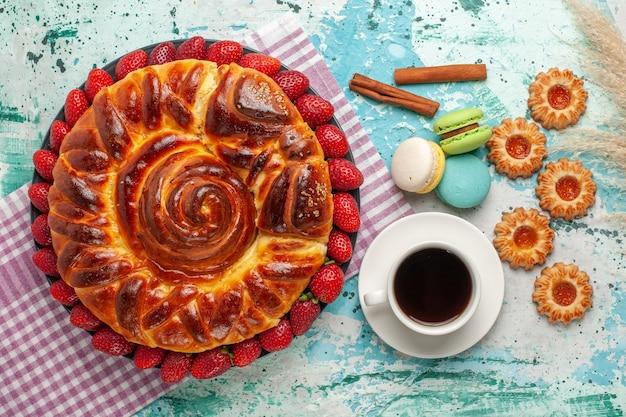 Vista de cima deliciosa torta com macarons de morangos vermelhos frescos e uma xícara de chá na superfície azul