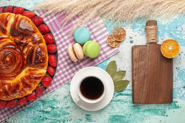 Vista de cima deliciosa torta com morangos vermelhos e uma xícara de chá na superfície azul