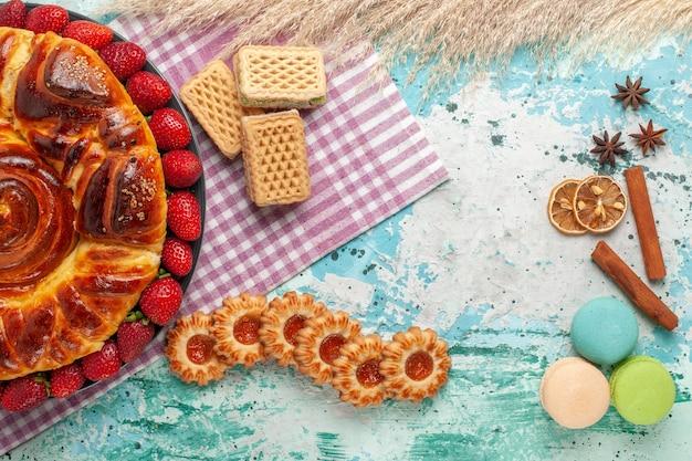 Vista de cima deliciosa torta com morangos vermelhos e waffles na superfície azul