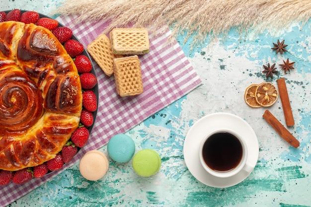 Vista de cima deliciosa torta com morangos vermelhos, macarons franceses e waffles na superfície azul