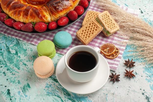 Vista de cima deliciosa torta com uma xícara de chá e morangos vermelhos frescos na superfície azul