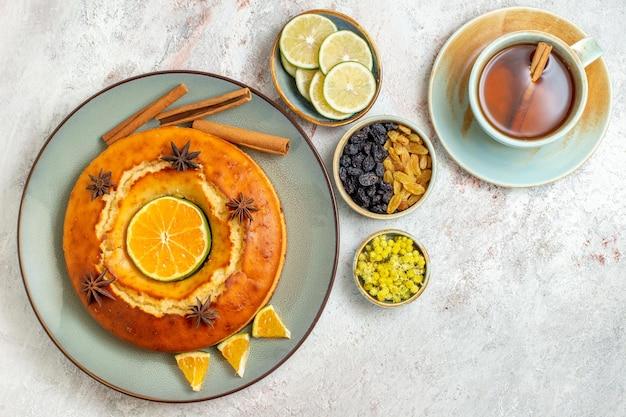 Vista de cima deliciosa torta com uma xícara de chá no fundo branco frutas doce nozes torta bolo biscoito Foto gratuita