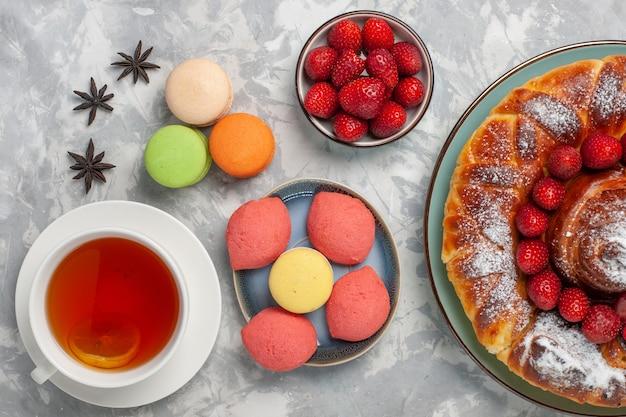 Vista de cima deliciosa torta de morango com bolinhos de macarons e xícara de chá na superfície branca torta de bolo biscoito doce açúcar chá assar