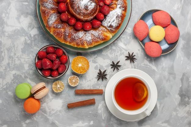 Vista de cima deliciosa torta de morango com bolinhos e xícara de chá na superfície branca biscoito bolo de açúcar torta doce assada
