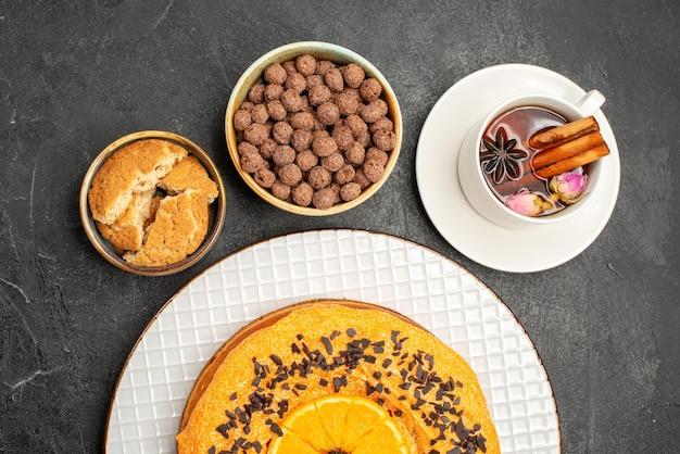 Vista de cima deliciosa torta doce com uma xícara de chá na superfície escura.