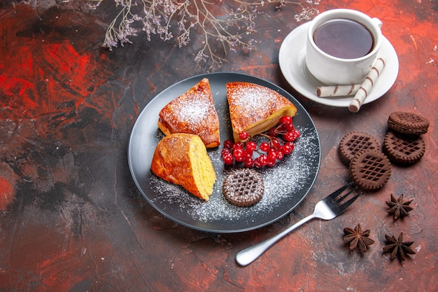 Vista de cima deliciosa torta fatiada com frutas vermelhas no chá de tortas doces de bolo de mesa escura