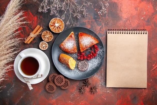 Vista de cima deliciosa torta fatiada com uma xícara de chá no chá de tortas doces de bolo de mesa escura
