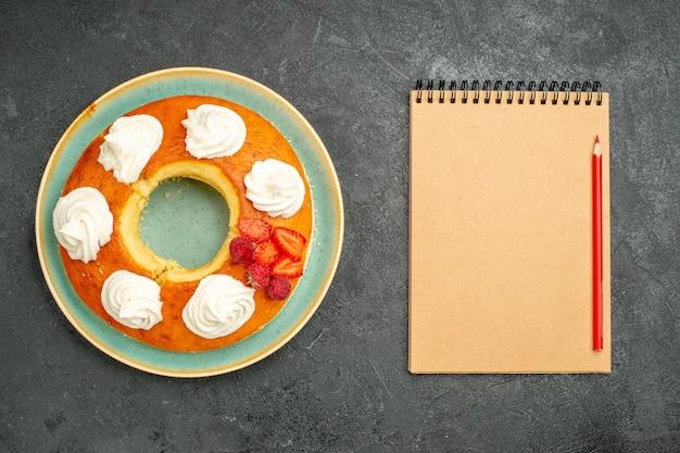 Vista de cima deliciosa torta redonda com frutas e creme no fundo escuro, chá, açúcar, biscoito, bolo, doce