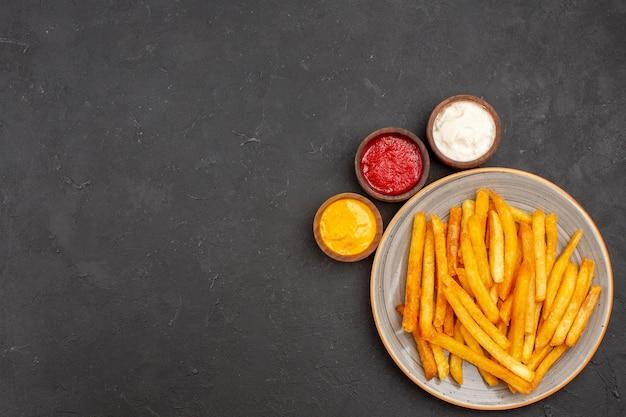 Vista de cima deliciosas batatas fritas com temperos em fundo escuro de batata hambúrguer fast-food