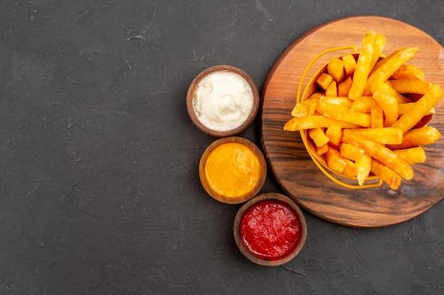Vista de cima deliciosas batatas fritas dentro de uma cesta com molhos no fundo escuro hambúrguer de lanche refeição de batata rápida