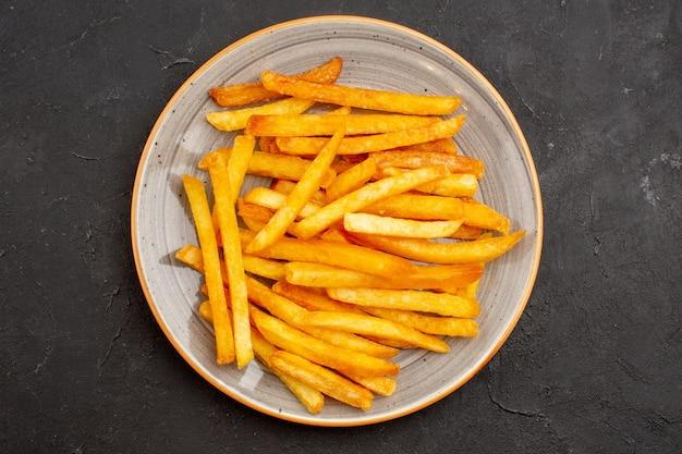 Vista de cima deliciosas batatas fritas dentro do prato no fundo escuro sanduíche de batata hambúrguer prato jantar