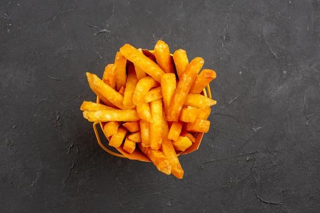 Vista de cima deliciosas batatas fritas em um fundo escuro refeição de hambúrguer prato de batata fast-food