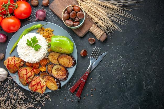 Vista de cima deliciosas berinjelas fritas com arroz cozido e passas em fundo escuro