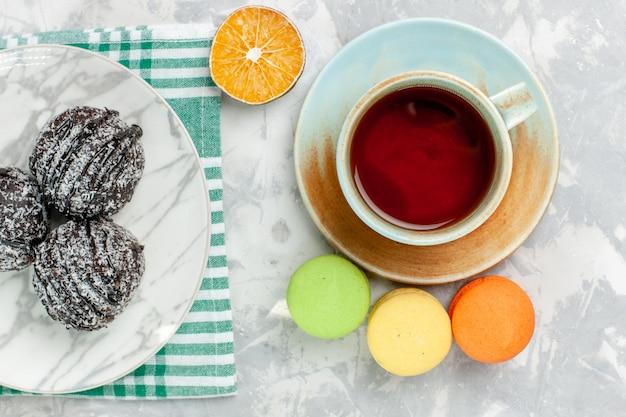Vista de cima deliciosas bolas de chocolate redondas em forma de bolos com chá de confeiteiro e macarons em uma mesa branca clara fazer bolo de chocolate e açúcar torta doce