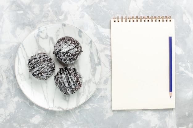 Vista de cima deliciosas bolas de chocolate redondas em forma de bolos com glacê e bloco de notas na mesa branca clara assar bolo de chocolate e açúcar torta