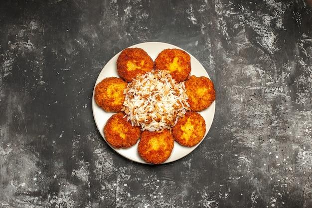 Vista de cima deliciosas costeletas fritas com arroz cozido na superfície escura refeição fotográfica de prato de carne