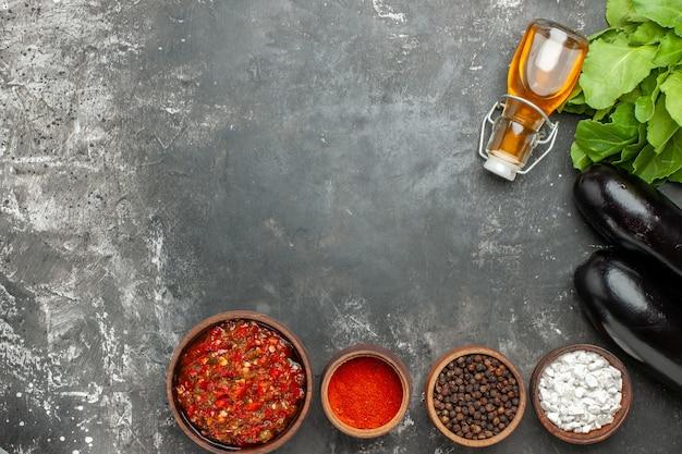 Vista de cima deliciosas especiarias diferentes de adjika em pequenas bawls berinjelas óleo em fundo cinza