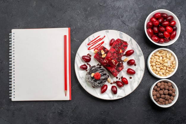 Vista de cima deliciosas fatias de bolo com nozes e dogwoods em uma mesa cinza
