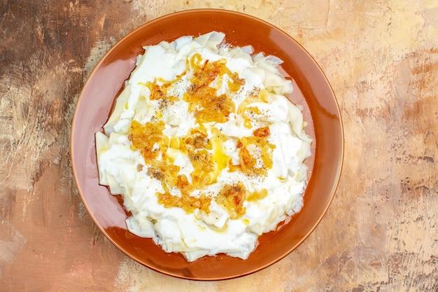 Vista de cima deliciosas fatias de massa com iogurte e óleo em superfície clara