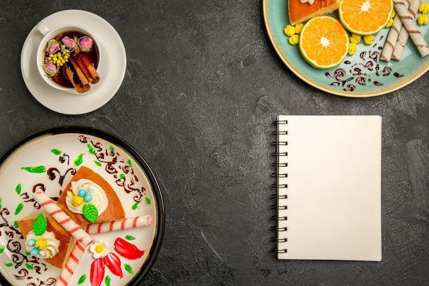 Vista de cima deliciosas fatias de torta com tangerinas frescas e uma xícara de chá no fundo cinza escuro torta fruta doce bolo massa chá