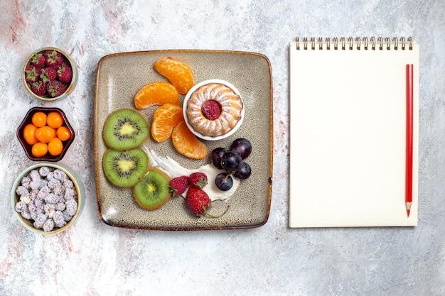 Vista de cima deliciosas frutas fatiadas com bolo e doces no fundo branco.