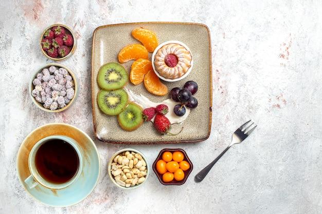 Vista de cima deliciosas frutas fatiadas com doces de bolo e uma xícara de chá no fundo branco.