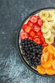 Vista de cima deliciosas frutas fatiadas dentro do prato na cor cinza exótica vida saudável foto amadurecida