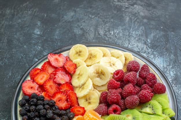 Vista de cima deliciosas frutas fatiadas dentro do prato na cor cinza exótica vida saudável foto suave árvore madura sombra