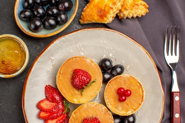 Vista de cima deliciosas panquecas com azeitonas e frutas no escuro