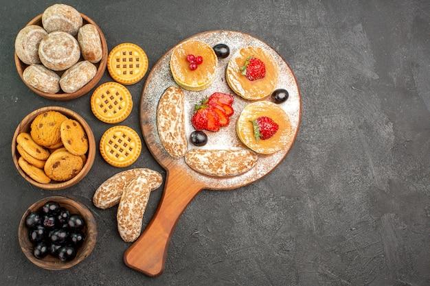 Vista de cima deliciosas panquecas com bolos doces e frutas em piso escuro