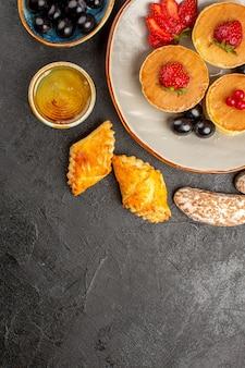 Vista de cima deliciosas panquecas com bolos e frutas no escuro