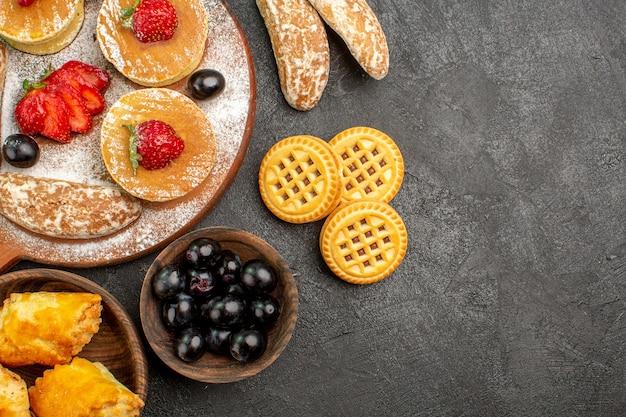 Vista de cima deliciosas panquecas com doces diferentes em uma sobremesa de bolo de açúcar com piso escuro