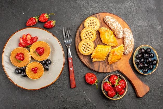 Vista de cima deliciosas panquecas com frutas e biscoitos em um bolo de superfície escura.