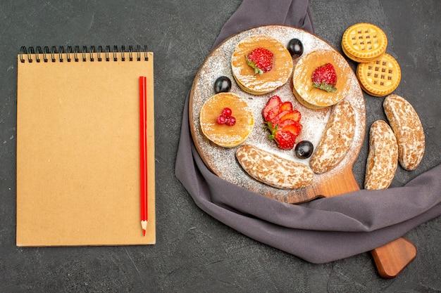 Vista de cima deliciosas panquecas com frutas e bolos doces em superfície escura bolo sobremesa doce